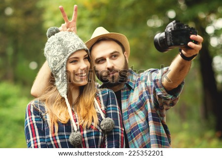 Cute hipster couple with hats taking a selfie with dslr camera in park in autumn. Closeup of young attractive blonde woman and bearded man posing for a self portrait outdoors.  - stock photo