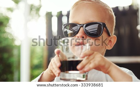 Cute hipster little boy in over sized sunglasses belonging to his mother or father sitting sipping a beverage in a glass on an outdoor patio - stock photo