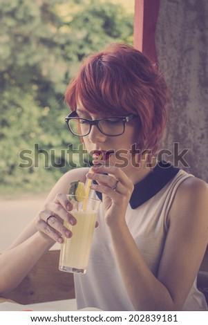 Cute hipster teenage girl in a coffee shop, daydreaming, enjoying lemonade. Retro styled imagery - stock photo
