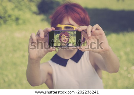 Cute hipster teenage girl taking a photo of herself with her smart phone, retro colors  - stock photo