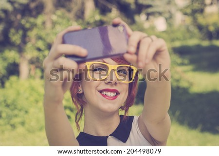 Cute hipster teenage girl taking a photo with her purple smart phone, retro colors