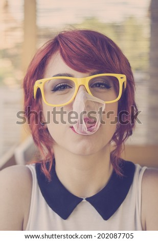 Cute hipster teenage girl with big chewing gum bubble popping over her face  - stock photo