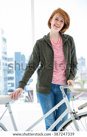 Cute hipster with her bike in front of a window - stock photo