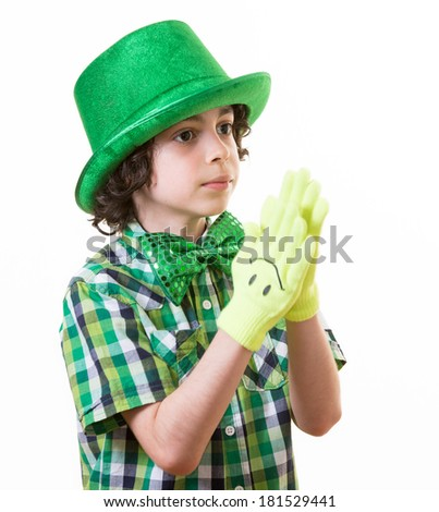 Cute Hispanic boy dressed for Saint Patrick celebrations and wearing smiley gloves over white backgruond