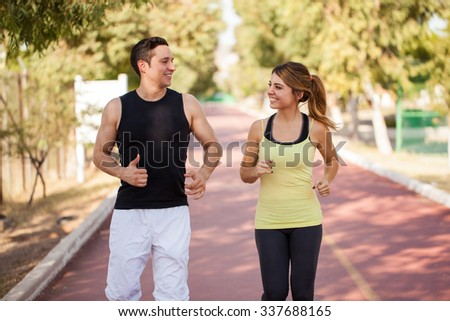 Cute Hispanic couple in sporty outfit working out and running together outdoors - stock photo