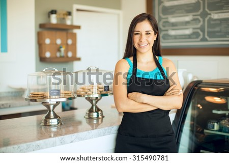 Cute Hispanic female business owner standing in front of her cake shop and smiling - stock photo
