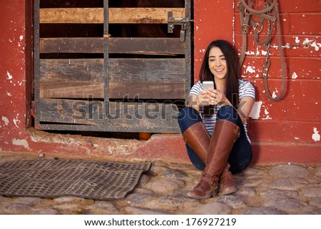 Cute Hispanic girl doing some social networking while spending some time at a stable - stock photo