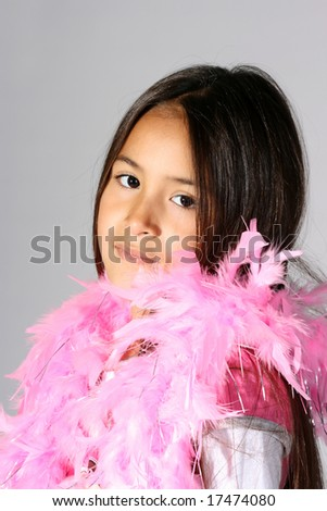 cute Hispanic girl playing dress-up with a pink boa