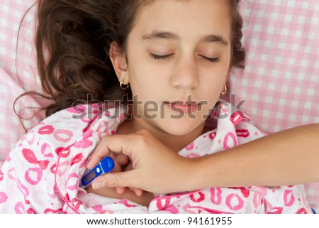 Cute hispanic girl sick with fever laying in her bed while a woman's hand measures her temperature with a thermometer