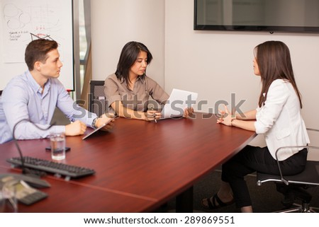 Cute Hispanic woman sitting in front of a couple of people during a job interview - stock photo