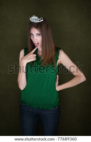 Cute homecoming queen with hand on hip and gagging gesture - stock photo