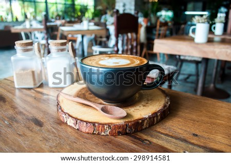 Cute Hot Cappuccino Coffee on wooden saucer in cafe - stock photo