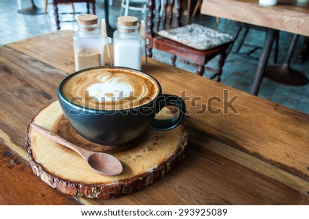 Cute Hot Latte Coffee on wooden saucer in cafe - stock photo