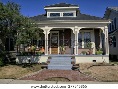 Cute house with brick walk way and plants on porch in New Orleans Louisiana