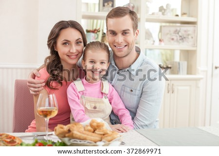 Cute husband and wife are dining with their child - stock photo