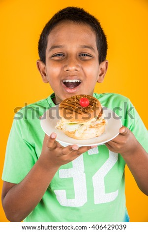 cute indian boy and burger in small white plate, small asian boy and burger, over yellow  background - stock photo
