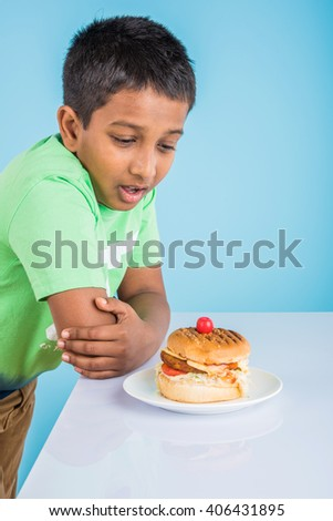 cute indian boy staring at burger served in white ceramic plate on white table , small asian boy and burger, over blue background - stock photo