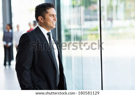 cute indian businessman looking outside window - stock photo