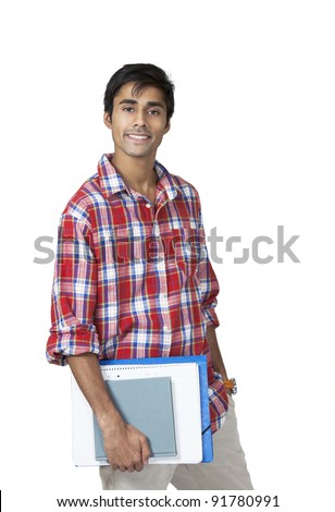 Cute indian college guy holding books and notes with carefree expression - stock photo