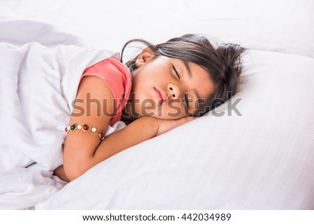 cute Indian Girl sleeping over white pillow, small asian girl sleeping on bed - stock photo
