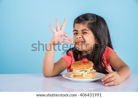 cute indian girl staring at burger served in white ceramic plate on white table , small asian girl and burger, over blue background - stock photo