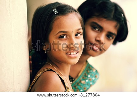 Cute Indian girls smiling at the camera.