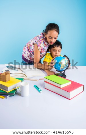cute indian kids studying, smart asian girl and boy doing home work, indian siblings studying, indian small girl helping her brother in doing homework - stock photo