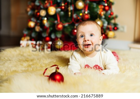 cute infant boy lies on the fur near the Christmas tree - stock photo