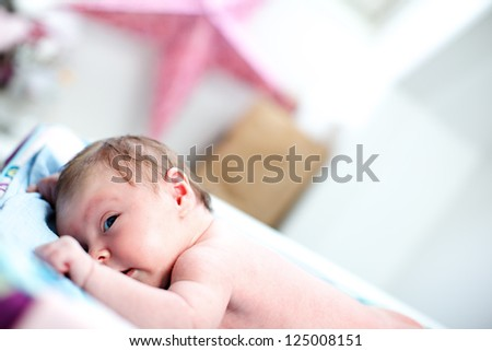 Cute inquisitive newborn baby lying on its stomach on a blanket keeping a watchful eye on its surroundings with copyspace - stock photo
