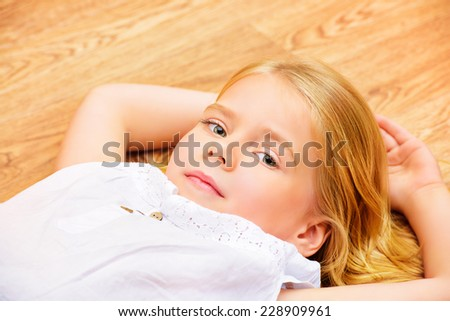 Cute joyful girl lying on a floor at home. - stock photo