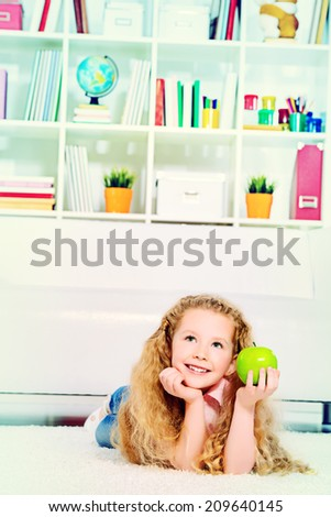 Cute joyful girl lying on a floor at home and and eating fresh apple. - stock photo