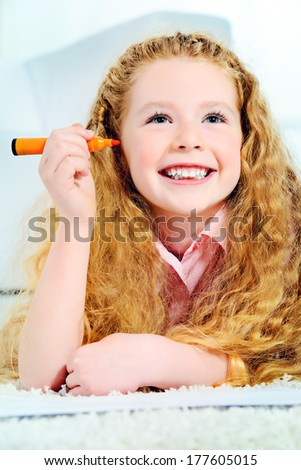 Cute joyful girl lying on a floor at home and drawing. - stock photo