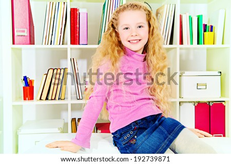 Cute joyful girl sitting on a sofa at home.