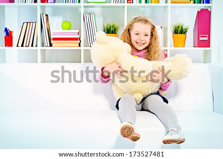 Cute joyful girl sitting on a sofa at home and playing with her teddy bear. - stock photo