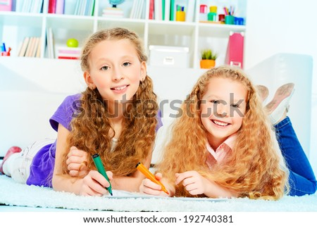 Cute joyful girls sisters lying on a floor at home and drawing. - stock photo