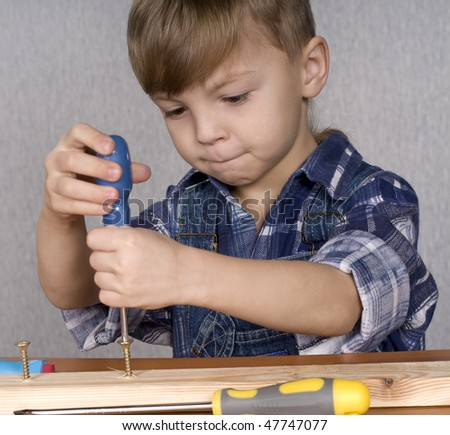 Cute kid as a construction worker, playing with tools