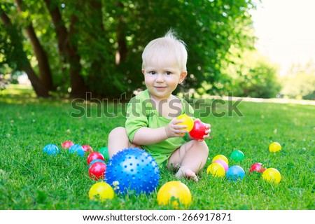 Cute kid baby boy sitting on grass in park, playing with balls and smiling - stock photo