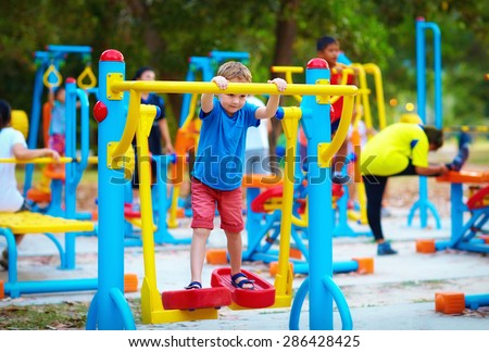 cute kid, boy exercising on sport ground with other people on background - stock photo