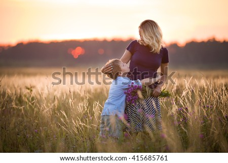 Cute kid boy hugging his mother on a summer meadow on beautiful summer sunset. Happy family together. Mum and child. Motherhood and childhood. Family walking in the field. Outdoors. - stock photo