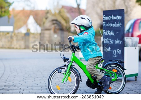 Cute kid boy of 5 years riding with his first green bike in the city. Happy child in colorful clothes. Active leisure for kids outdoors. - stock photo