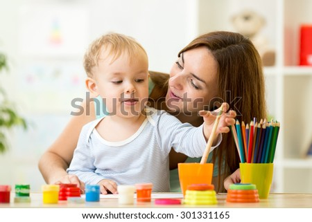 cute kid boy painting with paintbrush at home or day care center - stock photo