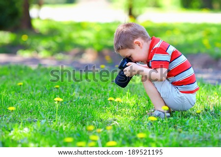 cute kid boy photographing flowers - stock photo