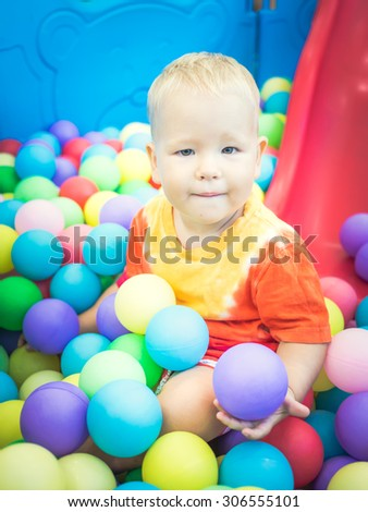 Cute kid boy playing with colorful balls  - stock photo