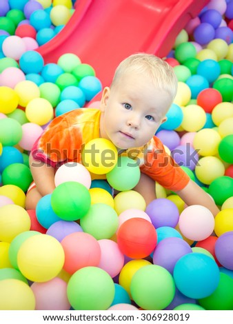 Cute kid boy playing with colorful balls