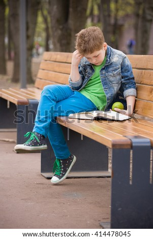 Cute kid boy sitting on a bench in the park and reading a book. Child learning and reading outdoors. School boy with a book outside. Back to school - stock photo