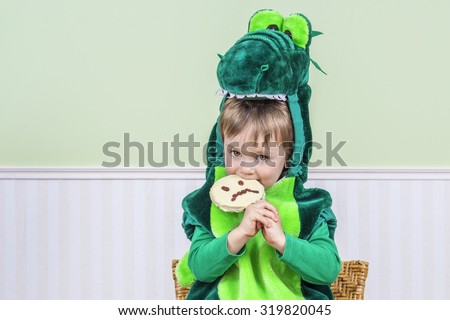 Cute kid eating a Halloween cookie - stock photo