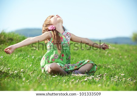 Cute kid girl at green field - stock photo