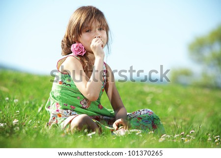 Cute kid girl at green field