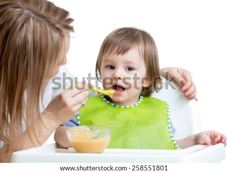 cute kid girl eating food with mother help