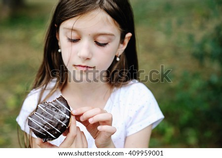Cute kid girl eating sweet donut outdoor in the park on sunny warm day. Focus on donut - stock photo